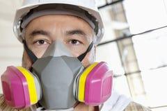 男性在建造场所的工作者佩带的防尘面具画象  免版税库存照片