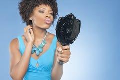 起皱可爱的非裔美国人的妇女,当看在色的背景时的镜子 免版税图库摄影