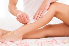 给妇女腿打蜡的美容师 免版税库存图片