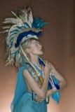 摆在色的背景的用羽毛装饰的成套装备的美丽的妇女 免版税库存照片