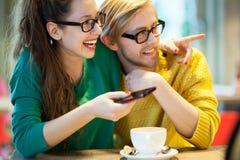 在咖啡馆的年轻夫妇,笑 图库摄影