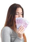 嗅到和拿着五百张欧洲钞票的美丽的妇女 免版税库存照片