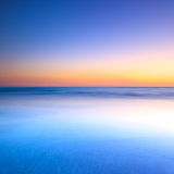 白色海滩和暮色日落的蓝色海洋 图库摄影