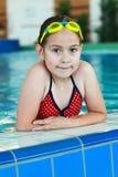 有风镜的女小学生在游泳池 库存照片