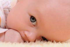 吃她的手的逗人喜爱的婴孩 免版税库存图片