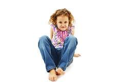 滑稽的小女孩坐在牛仔裤的地板 免版税库存照片