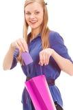 白肤金发的妇女在卡片放入袋子 免版税库存图片
