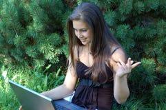 相当有膝上型计算机的女孩 免版税库存照片