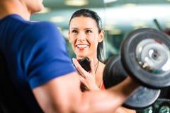 在健身房和哑铃训练的个人教练员 免版税库存图片