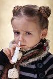 有流感的小女孩使用鼻孔喷射 库存照片
