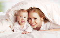 愉快的家庭。 使用在毯子之下的母亲和婴孩 免版税库存照片
