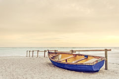 在白色海滩的老黄色蓝色木小船在温暖的日落 免版税库存照片