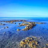 岩石在蓝色海洋在日出的清楚的天空下。 免版税库存照片