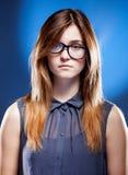 戴书呆子眼镜的失望的少妇,迷茫的女孩 免版税图库摄影