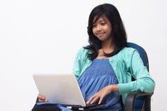 拿着膝上型计算机和享受她的工作的年轻女商人 库存照片