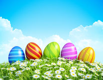 复活节背景用在草甸的华丽复活节彩蛋。 免版税图库摄影
