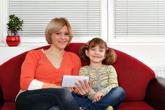 母亲和女儿坐与片剂个人计算机的床 库存照片