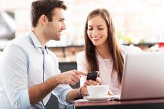 使用膝上型计算机的商人在咖啡馆 免版税图库摄影