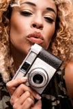 送飞吻的逗人喜爱的妇女,当拿着一台减速火箭的照相机时 免版税库存照片