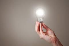 Рука с электрической лампочкой Стоковая Фотография