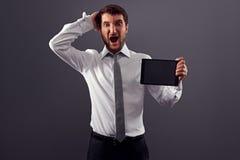尖叫震惊的人拿着片剂个人计算机和 库存图片