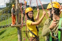 年轻夫妇在安全设备冒险公园 免版税库存图片