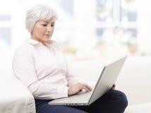 研究膝上型计算机的微笑的资深妇女 图库摄影