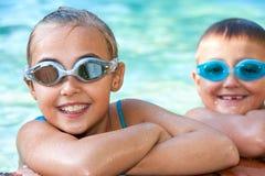 在游泳池的孩子与风镜。 库存图片