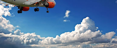 反对蓝天的喷气式客机与白色蓬松云彩 库存图片