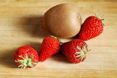 在砧板的草莓和猕猴桃 库存照片