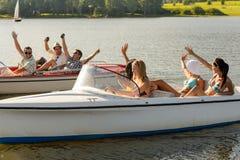 坐在汽艇夏令时的挥动的朋友 免版税库存照片