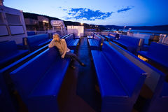 疲乏的女孩坐甲板 免版税库存照片