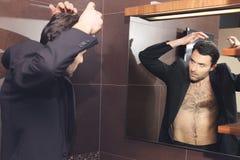 年轻英俊的商人做头发 免版税图库摄影