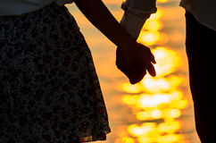 握有日出的恋人夫妇手 免版税库存图片