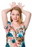 Όμορφο εύθυμο κορίτσι με τα δάχτυλα που είναι εξαπλωμένα στο κεφάλι του Στοκ Εικόνες