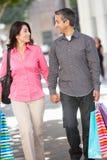 在城市街道上的夫妇运载的购物袋 图库摄影