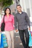 在城市街道上的夫妇运载的购物袋 免版税库存照片