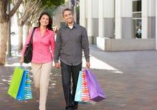 在城市街道上的夫妇运载的购物袋 免版税库存图片