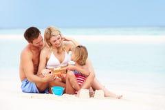 在使用的家庭在美丽的海滩 免版税库存照片
