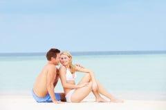 一起放松在美丽的海滩的夫妇 免版税库存照片