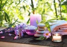 按摩在有紫罗兰色花、蜡烛和毛巾的竹庭院里 免版税图库摄影