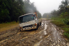 在泥泞的路的陷进的卡车 免版税图库摄影