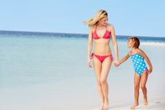 走在美丽的海滩的母亲和女儿 库存图片
