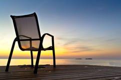 在一个码头的椅子在日出期间的海附近 免版税库存照片