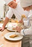 Θηλυκός αρχιμάγειρας που διακοσμεί το κέικ με την κτυπημένη κρέμα Στοκ Εικόνα