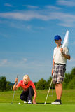 打在路线的年轻嬉戏夫妇高尔夫球 免版税库存照片