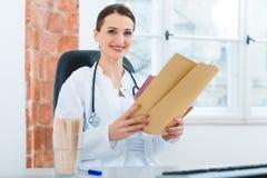 在文件的女性医生读书 免版税库存图片