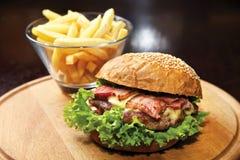Вкусный гамбургер с говядиной и беконом на плите Стоковая Фотография RF