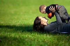 一个愉快的家庭。有婴孩的年轻母亲 库存照片