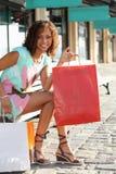 妇女坐一个长木凳 免版税库存图片